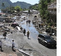 People walk along scene of devastation following powerful quake in Pago Pago village on American Samoa, 30 Sep 2009
